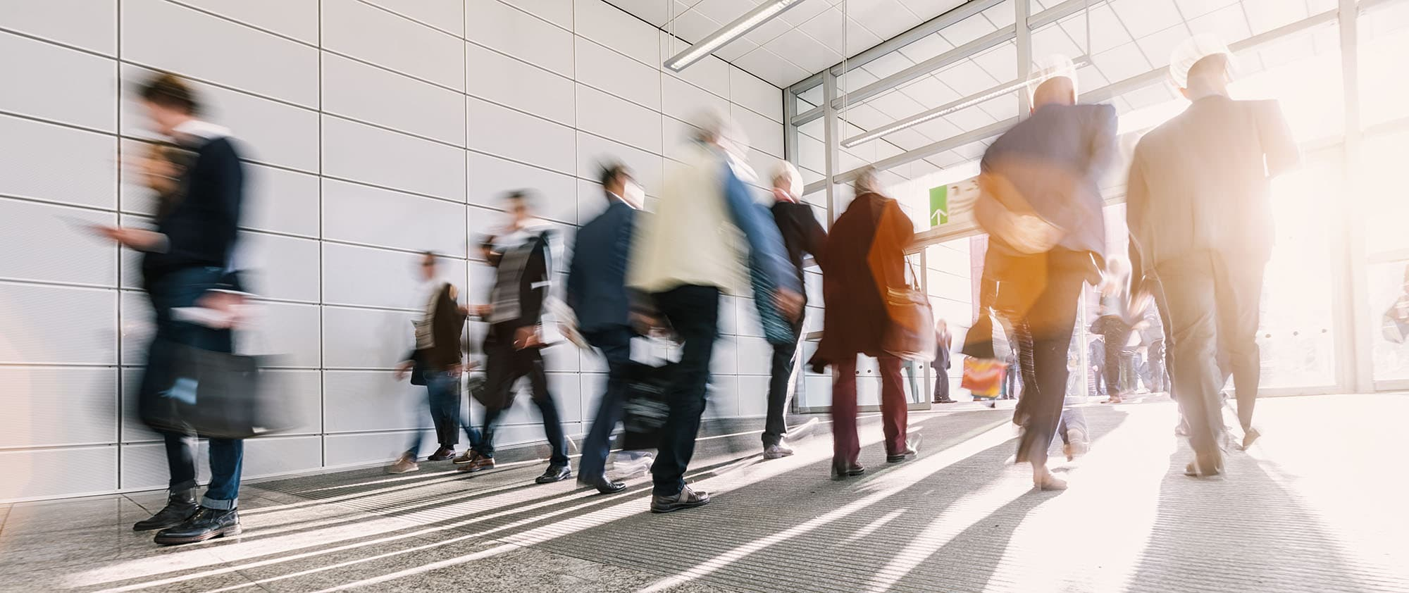 stock image of a dozen or so blurred business people walking in and out of a bright modern building`